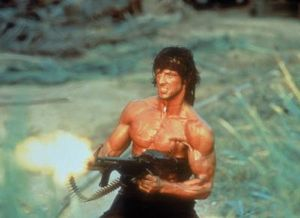 Stallone as Rambo, muscular and firing a machine gun